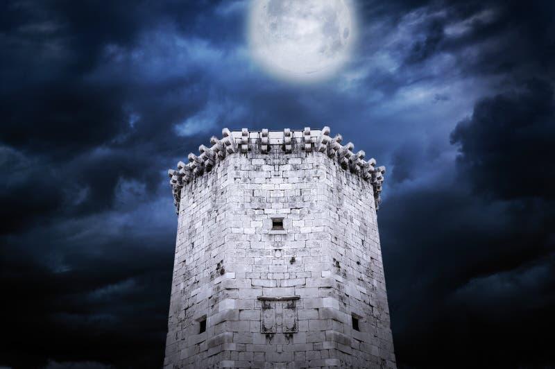 Toren van kasteel bij nacht in het maanlicht stock afbeelding