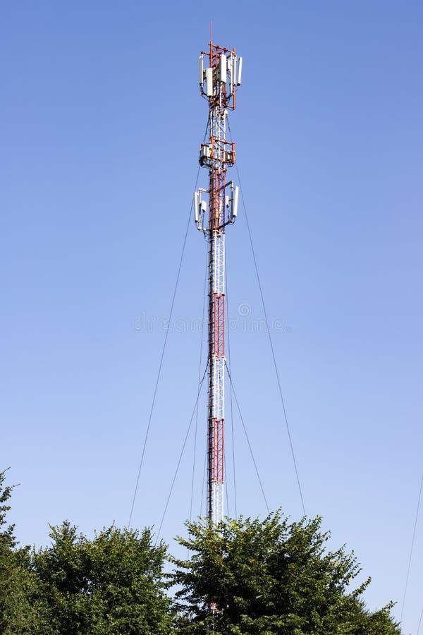 Toren van mededeling tegen de hemel en de groene bomen stock afbeelding