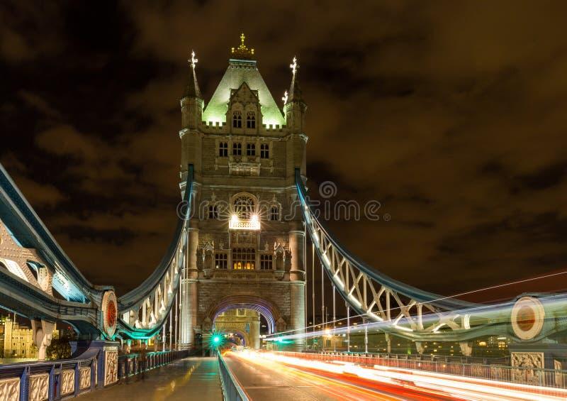 Torenbrug in Londen, het UK bij nacht met het bewegen van rode dubbeldekkerbus die lichte sporen verlaten royalty-vrije stock foto