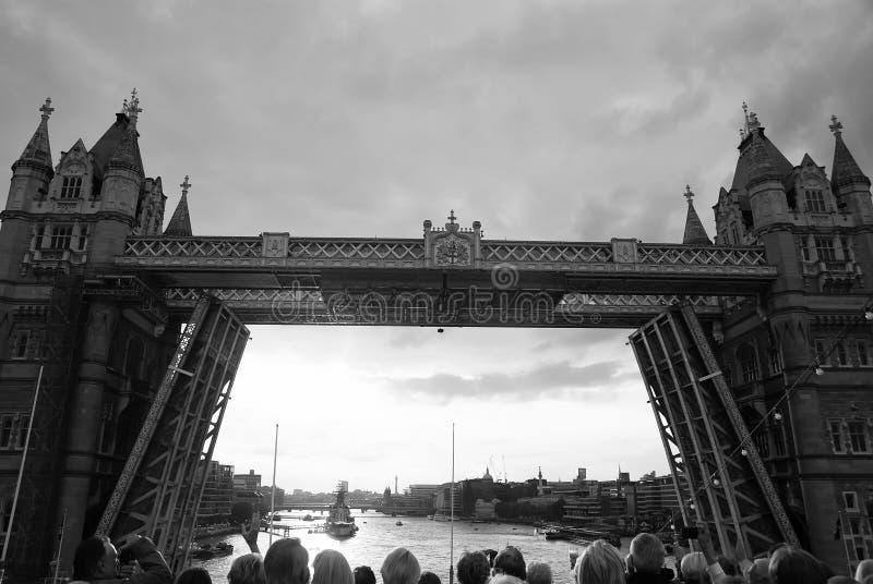 Torenbrug worden die die in Londen, het Verenigd Koninkrijk wordt geopend De mensen bekijken brug over de rivier van Theems op gr stock afbeeldingen