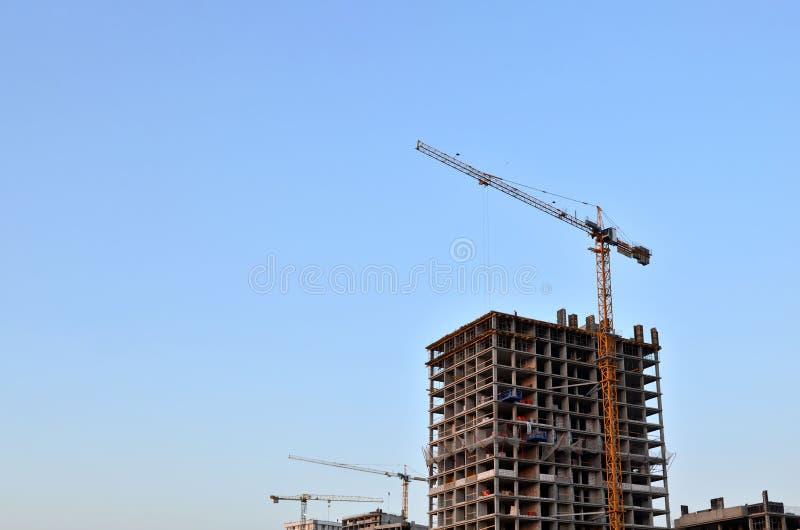 Torenkranen die een nieuw gebouw construeren bij een bouwwerf op de zonsondergang en de blauwe hemelachtergrond royalty-vrije stock fotografie