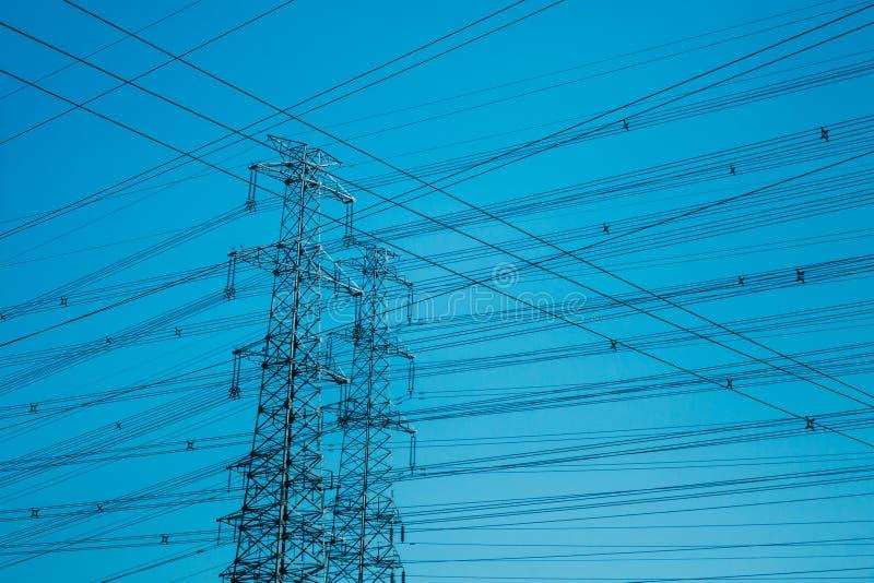 Torens met hoog voltage die tegen blauw worden gesilhouetteerd stock foto's