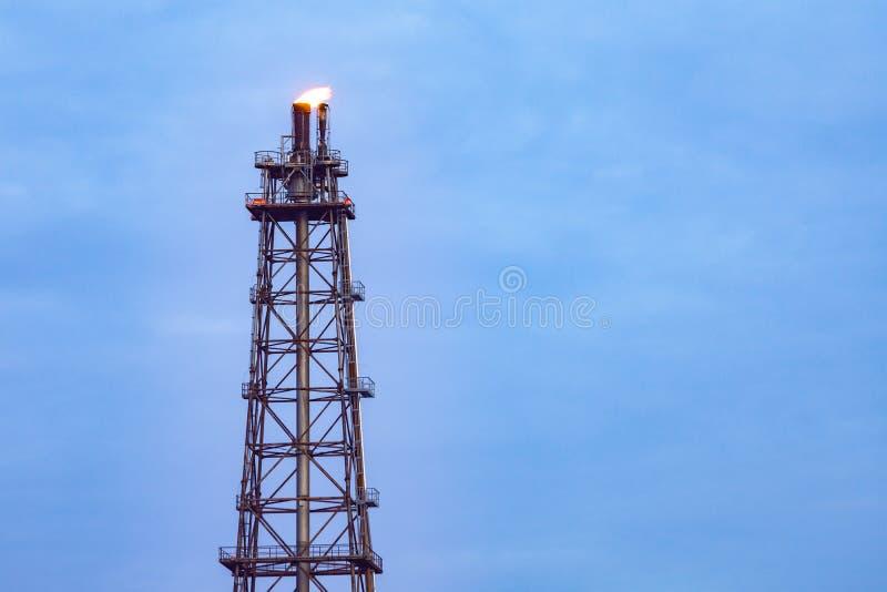 Torenschoorsteen van Olieraffinaderij met brand op bovenkant op blauwe wolkenhemel stock afbeelding
