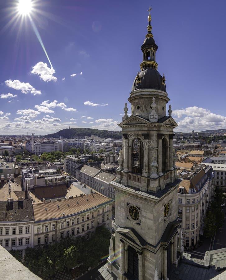 Torenspits van St Stephen Kathedraal met de zon op hoogte en de duidelijke hemel, Boedapest, Hongarije stock afbeelding