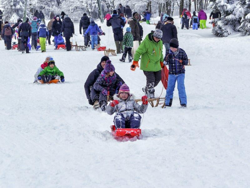 Torfhaus, Deutschland - 3 JANUAR 2015: Leute mit Kindern gehen, auf dem Berg zu rodeln Wintersportwochenende der Familie aktives stockbild