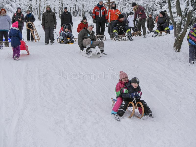 Torfhaus, Germany - 3 JANUAR 2015: Children going down a hill in the snow. Family active sports rest in winter. Winter landscape stock photo