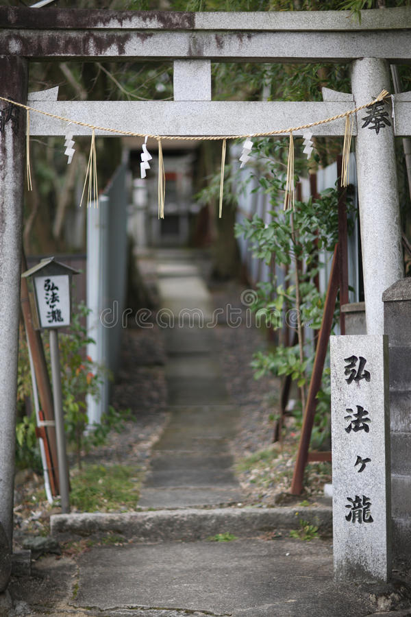 Torii gate. Stone Torii gate with the name donator and ritual zigzag pieces of paper and rope with tassels stock photo