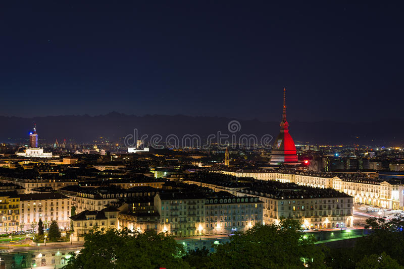 Torino (Turin, Italy), garnet colored Mole Antonelliana. Turin, Italy - May 4, 2016: Night cityscape of Torino (Turin, Italy). The Mole Antonelliana glowing with stock photo