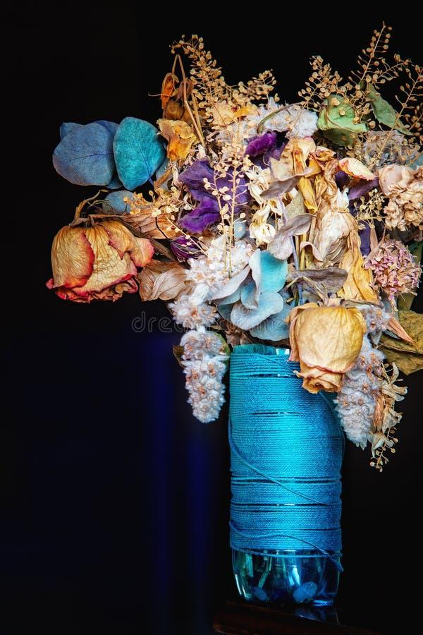 Torkad blommabukett i en blå vas arkivbilder