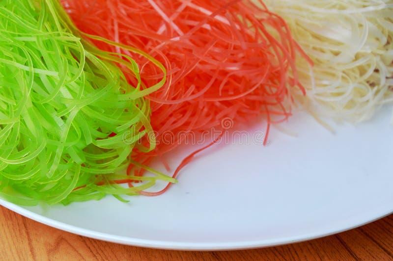 Torkad färgrik thailändsk risnudel på den vita plattan royaltyfria foton