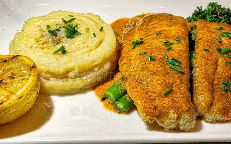 Torkad fisk och potatis på plattan arkivbild