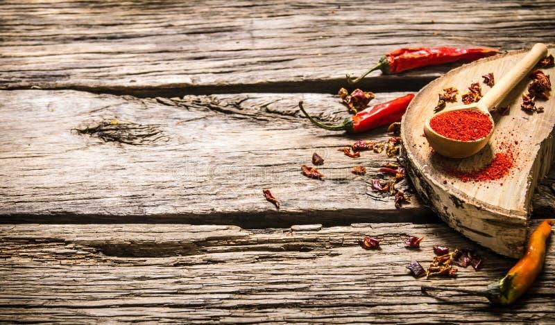 Torkad och mald peppar för röd chili på ekställning arkivfoton