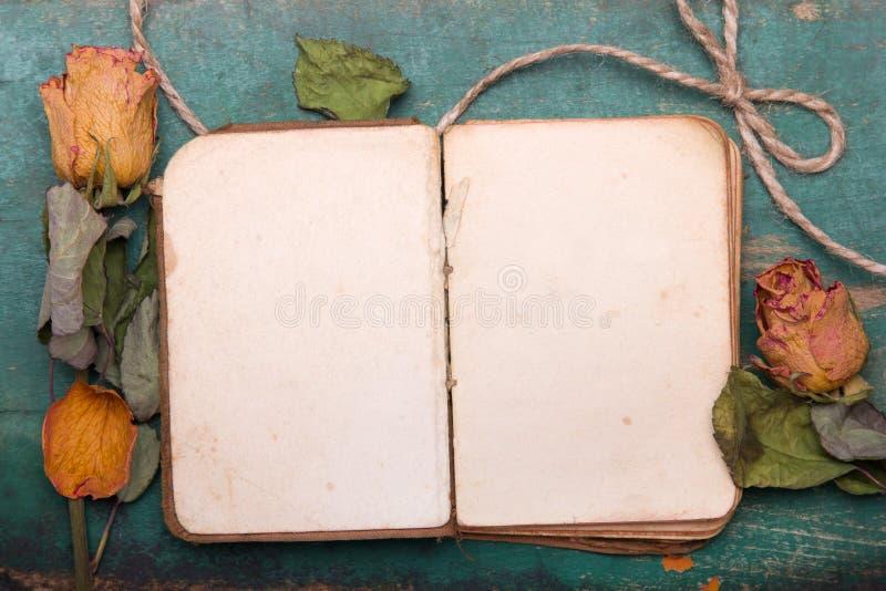 Torkad orange rosor och gammal bok på träbakgrund, arkivfoton