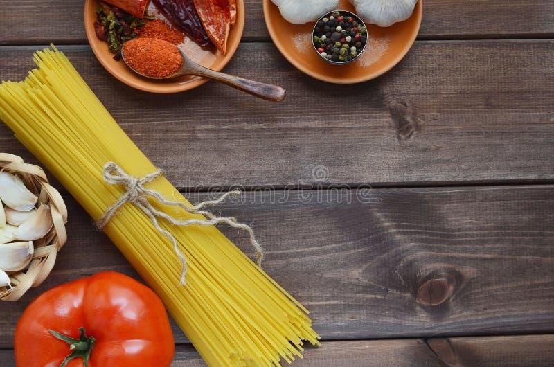 Torkad pasta på en träbakgrund med kryddor royaltyfri foto