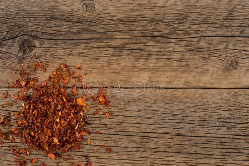 Torkad röd peppar på den gamla trätabellen royaltyfria foton