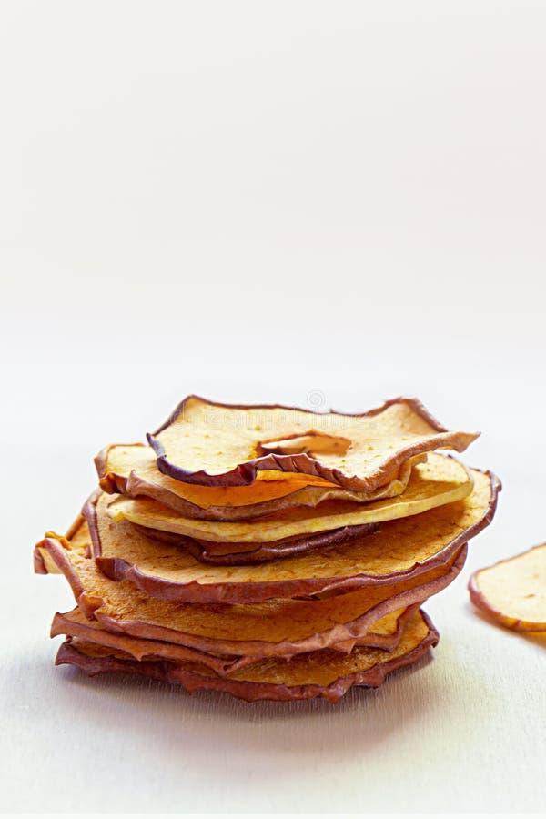 Torkade torkade äpplechiper på den vita trätabellen Sunt strikt vegetarianmellanm?l arkivfoton