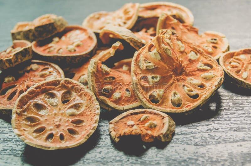 Torkade örter och torkad baelfrukt, närbild av bael som är torr på trägolvet arkivfoto