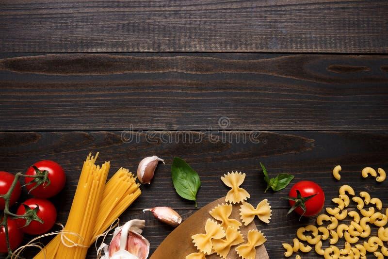 Torkade blandade pasta och grönsaker på den mörka träbästa sikten för tabell, med kopieringsutrymme royaltyfri foto