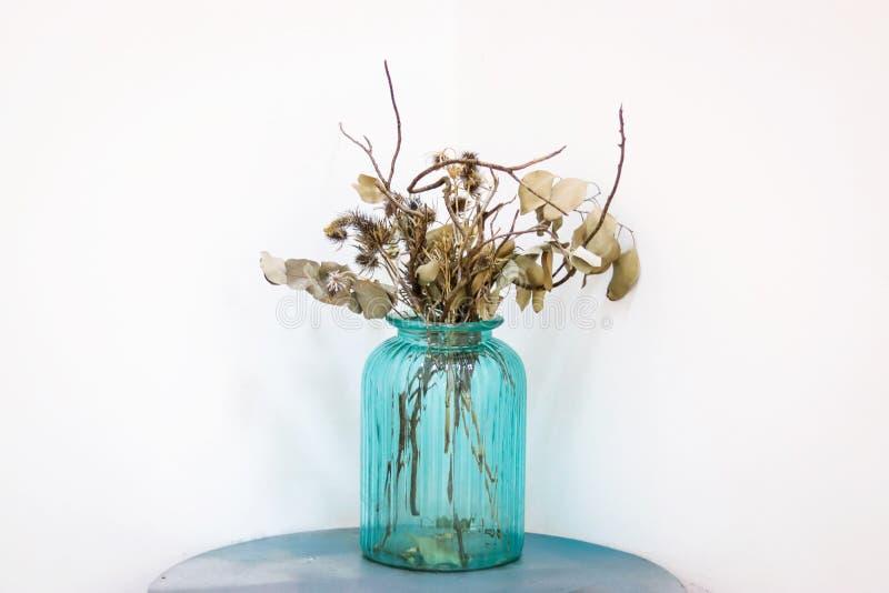 Torkade blommor i den bl?a exponeringsglaskruset arkivbild