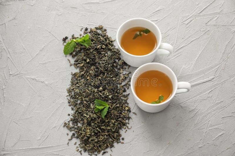 Torkade gröna teblad och koppar av den aromatiska drinken på ljus bakgrund royaltyfria foton