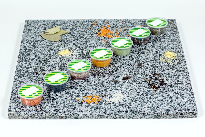 Torkade kryddor i plast- behållare på en marmorbakgrund arkivfoton