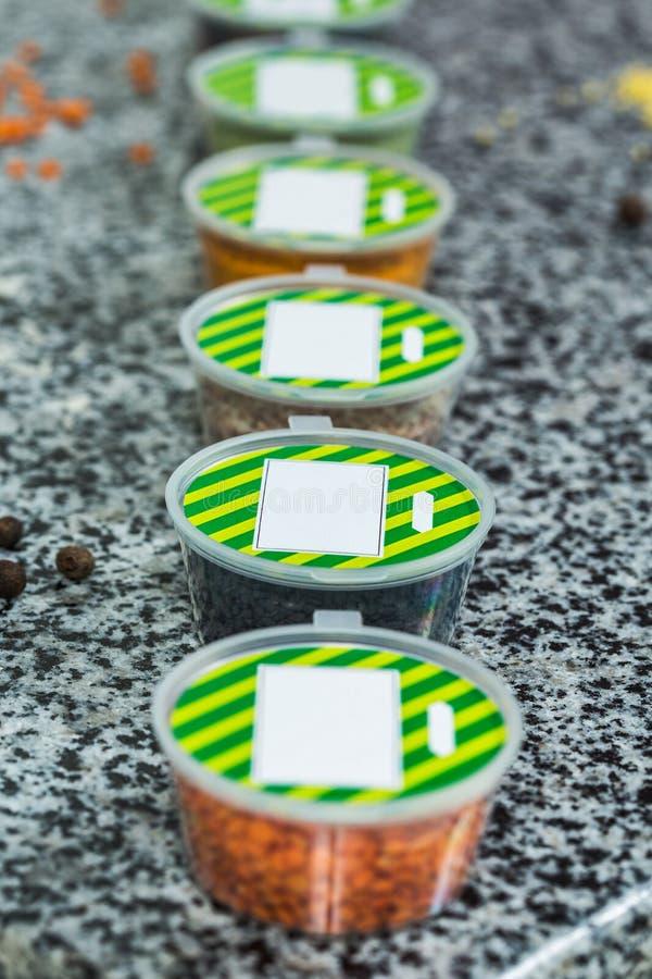 Torkade kryddor i plast- behållare på en marmorbakgrund arkivfoto