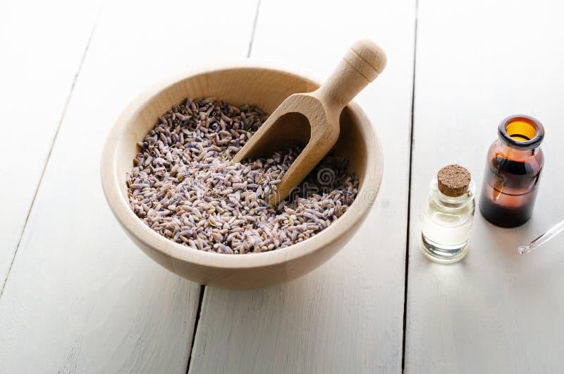 Torkade lavendelörter med små medicinflaskor av olja på den träPlanked tabellen arkivfoto