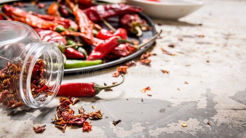 Torkade peppar för röd chili på ett magasin och i kruset royaltyfri foto