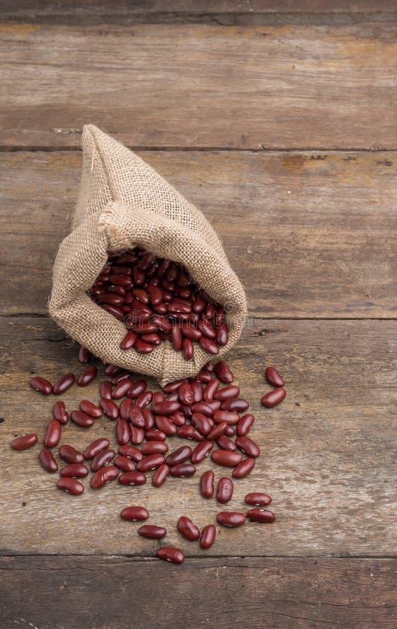 Torkade röda bönor i säckväv plundrar, röda bönor i säckvävpåse arkivfoton