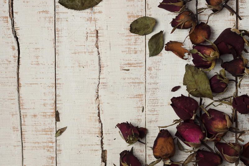 Torkade rosor på vita parkettplankor arkivfoto