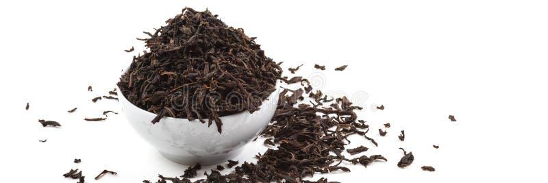 Torkade teblad i keramisk kopp ?ver vit bakgrund arkivfoto