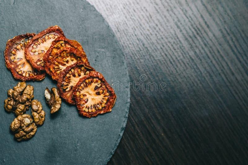 Torkade tomatvaln?tter p? m?rka bakgrunder royaltyfri foto