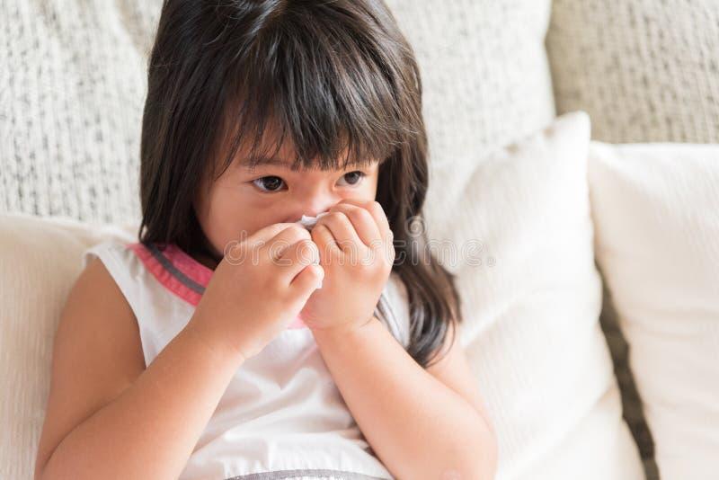 Torkande eller rengörande näsa för sjuk liten asiatisk flicka med silkespappersitti royaltyfria foton