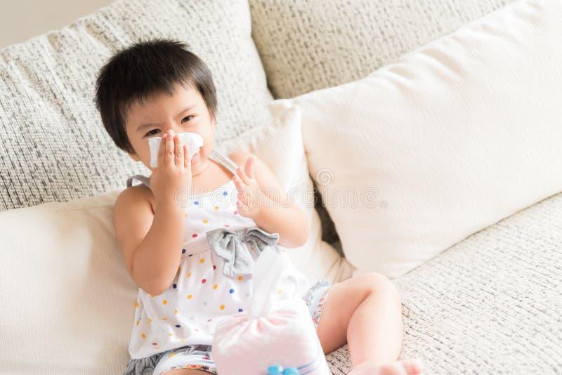 Torkande eller rengörande näsa för sjuk liten asiatisk flicka med silkespappret arkivbilder