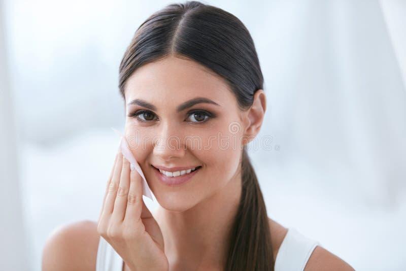 Torkar den rengörande framsidan för kvinnan med ansikts- rentvå och att ta bort makeup royaltyfri foto
