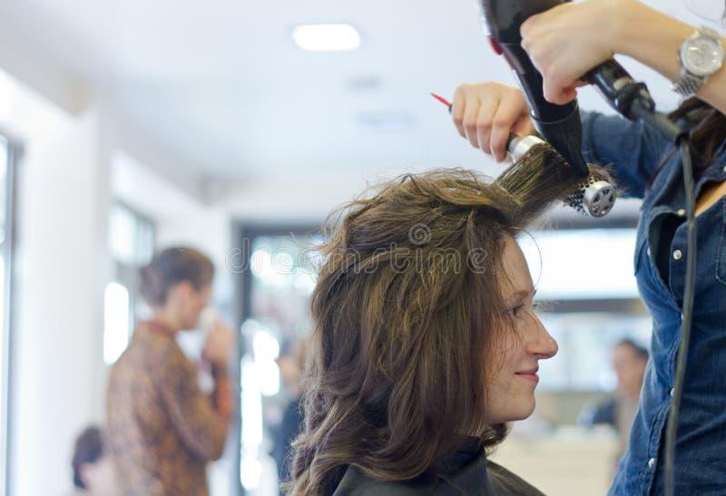 Torkar hår i salong royaltyfri fotografi