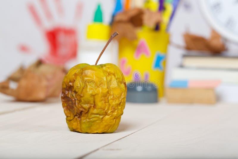 Torkat grönt äpple på en träyttersida arkivbild