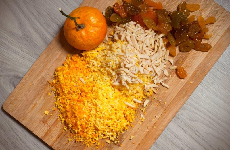 Torkat russin, högg av mandlar och krossade mandarinskal på träbräde över grå träbakgrund, bästa sikt Ingrediens f?r royaltyfri foto