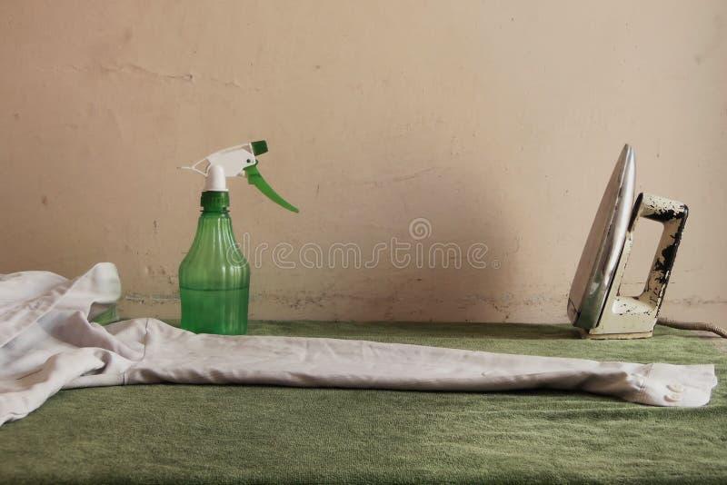 Torkdukestrykningtabell med skjortamuffen som är ordnad för att stryka och järn- och vattenatomiser fotografering för bildbyråer