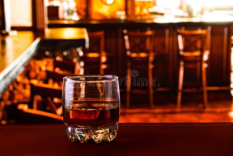 Torktumlareexponeringsglas med whisky på den röda tabellen arkivfoton