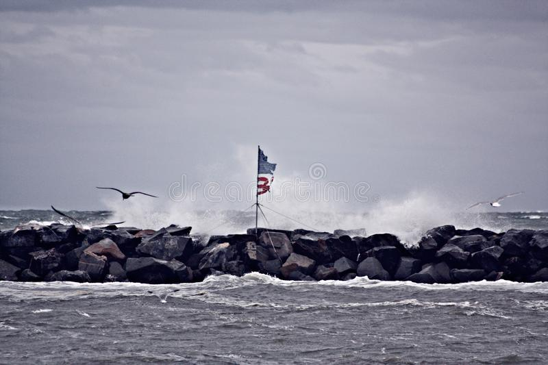 Tormenta del mar y bandera americana fotografía de archivo