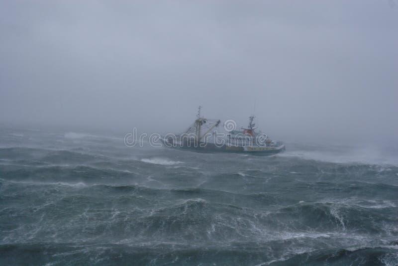 Tormenta, lluvia y un barco de pesca. foto de archivo