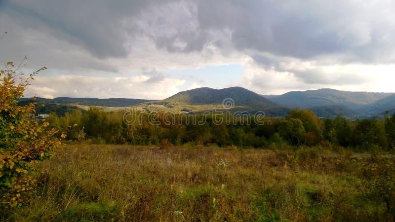 Tormenta sobre las montañas en la estación de verano con el prado verde iluminado del Sun foto de archivo libre de regalías