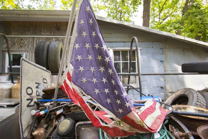 Torn American flag in junkyard. Shredded and tattered American flag on pile of rubbish in junkyard stock image