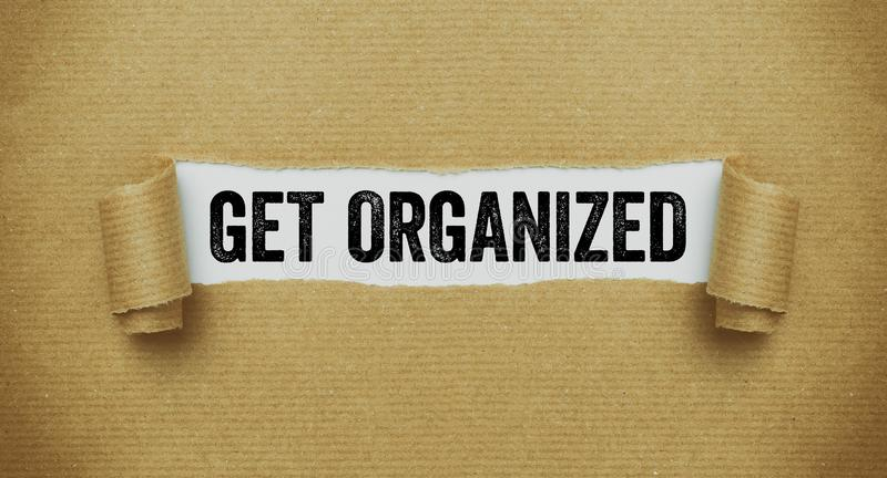 Torn brown paper revealing the words Get organized stock images