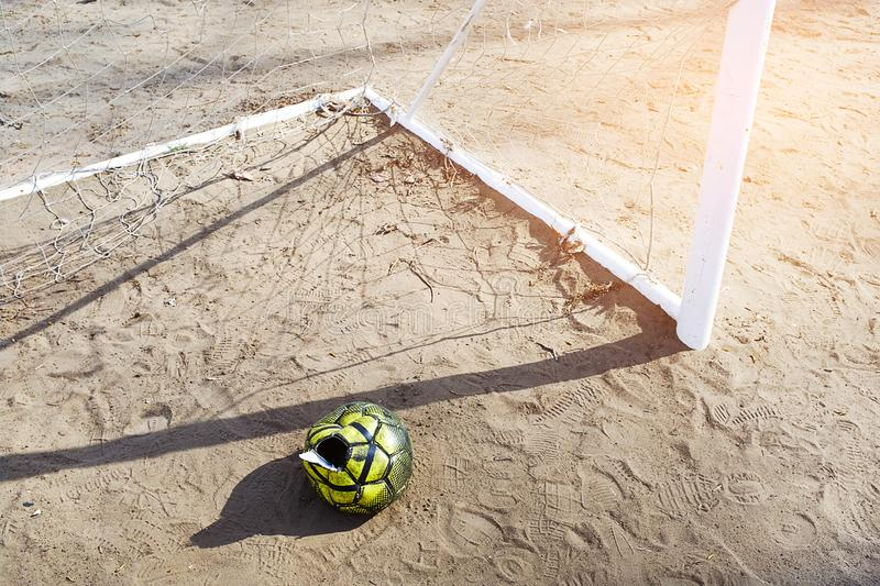 A torn deflated ball on the sand, near the football goal on a Sunny summer day, forgotten or thrown on the football field. Sports. Background with copy space royalty free stock photo
