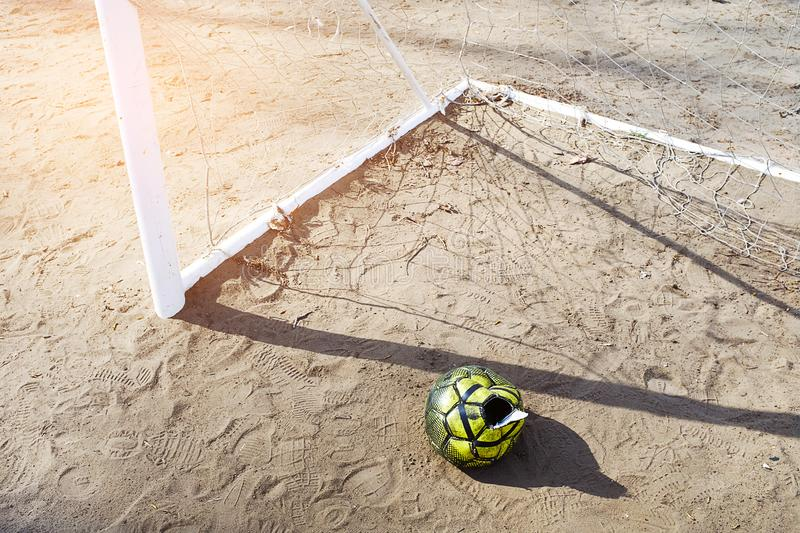A torn deflated ball on the sand, near the football goal on a Sunny summer day, forgotten or thrown on the football field. Sports. Background with copy space stock photography