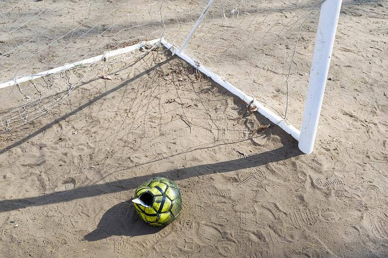A torn deflated ball on the sand, near the football goal on a Sunny summer day, forgotten or thrown on the football field. Sports. Background with copy space royalty free stock image