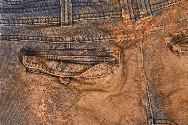 Trousers with mud. Torn and dirty working trousers covered in mud and clay, back side stock image