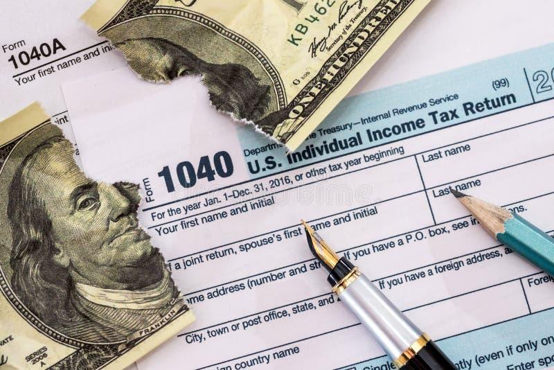 Torn dollar on usa 1040 tax form stock photo